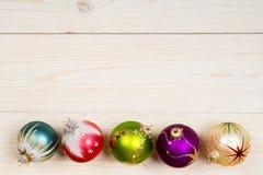 Weihnachtsbunte Bälle auf hölzernem Hintergrund Lizenzfreie Stockbilder