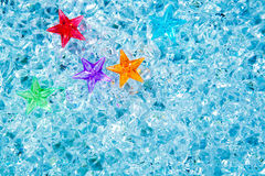 Weihnachtsbunte Glassterne auf kaltem blauem Eis Stockbilder