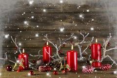 Weihnachtsdekoration auf hölzernem rustikalem Hintergrund: rote brennende Anzeige vier Stockfotografie