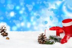 Weihnachtsdekoration auf Schnee mit blauem Winterhintergrund der Unschärfe S stockfotografie