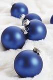 Weihnachtsdekoration, blauer Weihnachtsflitter auf weißer Pelzdecke Stockfotografie