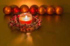 Weihnachtsdekoration - brennende rote Kerze, Weihnachtskranz, Flitter auf goldenem Hintergrund stockbilder
