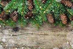 Weihnachtsdekoration des Tannenbaums und des Nadelbaumkegels auf strukturiertem hölzernem Hintergrund, magischer Schneeeffekt