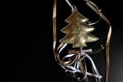Weihnachtsdekoration, die einen goldenen Baum mit dem farbigen Schnüren lokalisiert auf schwarzem Hintergrund darstellt stockbilder