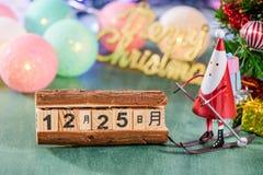 Weihnachtsdekoration, Eislaufweihnachtsmann mit Weihnachtsbildern an am 25. Dezember lokalisiert auf grünem Hintergrund Lizenzfreie Stockfotos