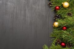 Weihnachtsdekoration, Girlandenrahmen-Konzepthintergrund, Draufsicht mit Kopienraum auf schwarzer hölzerner Tischplatte Stockfoto