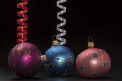 Weihnachtsdekoration mit bunten Bällen und Bändern auf schwarzem Hintergrund Lizenzfreie Stockbilder