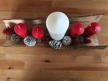 Weihnachtsdekoration mit den Kiefernkegeln gefärbt und den weißen und roten Steinen der Kerzen auf Holz stockfoto