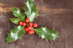 Weihnachtsdekoration mit den Stechpalmenblättern und -beeren, lokalisiert auf einem hölzernen Hintergrund Stockfoto