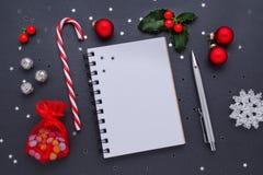 Weihnachtsdekoration mit einem leeren Notizbuch und Stechpalmenbeeren auf Schwarzem Lizenzfreie Stockfotografie