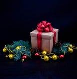 Weihnachtsdekoration mit Geschenk auf dunklem Hintergrund Stockfotografie