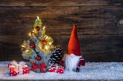 Weihnachtsdekoration mit Geschenkboxen, Weihnachtsbaum und lustigem Weihnachtsmann-Gnomen Lizenzfreie Stockfotografie
