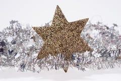 Weihnachtsdekoration mit goldenem Stern auf Lamettagirlande Lizenzfreies Stockbild