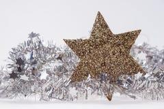 Weihnachtsdekoration mit goldenem Stern auf Lamettagirlande Lizenzfreie Stockfotos