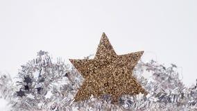 Weihnachtsdekoration mit goldenem Stern auf Lamettagirlande Stockfotos