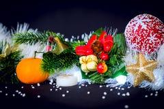 Weihnachtsdekoration mit grüner Kiefer, orange Mandarine am schwarzen Hintergrund Stockfotos