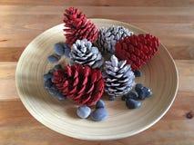 Weihnachtsdekoration mit Kiefernkegeln färbte die weißen und roten Steine auf Holz stockbild