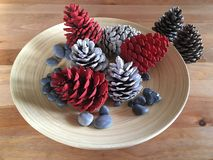 Weihnachtsdekoration mit Kiefernkegeln färbte die weißen und roten Steine auf Holz stockbilder