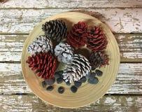 Weihnachtsdekoration mit Kiefernkegeln färbte die weißen und roten Steine auf Holz lizenzfreie stockbilder