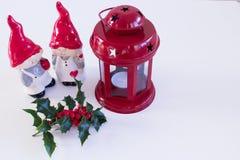 Weihnachtsdekoration mit roter Laterne und Stechpalme Porzellan-Figürchen, sehr reizend Jungen- und Mädchenelfen, auf weißem back Lizenzfreies Stockbild