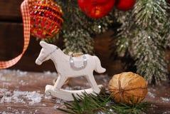 Weihnachtsdekoration mit Schaukelpferdspielzeug auf hölzernem backgroun Stockfotografie