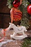 Weihnachtsdekoration mit Schaukelpferdspielzeug auf hölzernem Hintergrund Stockfotografie