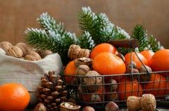 Weihnachtsdekoration mit Tangerinen und Nüssen mit copyspace auf woode Stockfotos