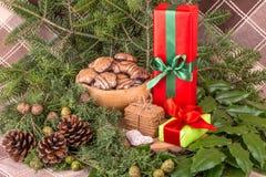 Weihnachtsdekoration mit Tannenzweigen, Mistelzweig, hölzernen Plätzchen und Geschenken Lizenzfreies Stockbild