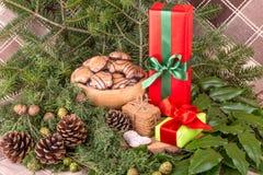 Weihnachtsdekoration mit Tannenzweigen, Mistelzweig, hölzernen Plätzchen und Geschenken Stockbild