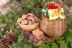 Weihnachtsdekoration mit Tannenzweigen, Mistelzweig, hölzernen Plätzchen und Geschenken Stockbilder