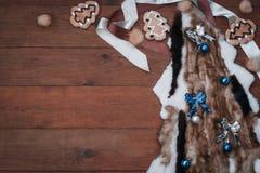 Weihnachtsdekoration Pelz des dekorativen Weihnachtsbaums, der Weihnachtsdekorationen, der Kekse und des Bandes auf braunem Hinte Stockfotografie