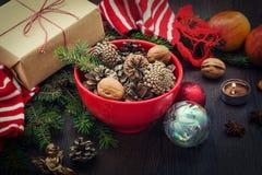 Weihnachtsdekoration - rote Schüssel voll Tannenzapfen, die Geschenkbox, die im Kraftpapier eingewickelt wird, Kiefer verzweigt s Lizenzfreie Stockbilder