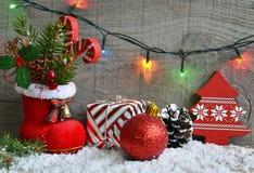Weihnachtsdekoration: roter Sankt-` s Stiefel, Tannenbaum, Girlande, Geschenk, Kiefernkegel und Spielwaren auf hölzernem Hintergr Stockbild
