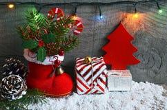Weihnachtsdekoration: roter Sankt-` s Stiefel, Tannenbaum, Girlande, Geschenk, Kiefernkegel und Spielwaren auf hölzernem Hintergr Lizenzfreie Stockfotografie