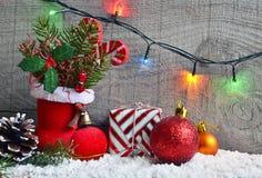 Weihnachtsdekoration: roter Sankt-` s Stiefel, Tannenbaum, Girlande, Geschenk, Kiefernkegel und Spielwaren auf hölzernem Hintergr Stockbilder