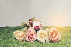 Weihnachtsdekoration von Santa Claus mit Blumen auf grünem Gras Stockfoto