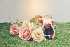 Weihnachtsdekoration von Santa Claus mit Blumen auf grünem Gras Lizenzfreie Stockbilder