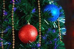 Weihnachtsdekorationen auf dem Weihnachtsbaum auf dem Hintergrund von farbigen Lichtern stockfotos