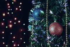Weihnachtsdekorationen auf dem Weihnachtsbaum auf dem Hintergrund von farbigen Lichtern stockbilder