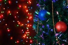 Weihnachtsdekorationen auf dem Weihnachtsbaum auf dem Hintergrund von farbigen Lichtern stockfoto