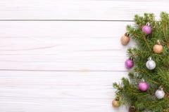 Weihnachtsdekorationen, auf einem Fichtenzweig auf einer weißen hölzernen Rückseite lizenzfreies stockfoto