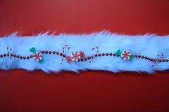 Weihnachtsdekorationen auf einem Streifen des weißen Pelzes mit einem roten Hintergrund Lizenzfreie Stockfotos