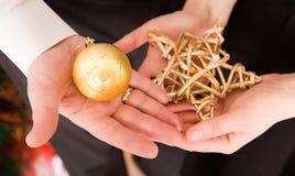 Weihnachtsdekorationen in den Händen des Mannes und der Frau Lizenzfreie Stockfotos