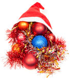Weihnachtsdekorationen fallen heraus von rotem Sankt-Hut Stockfotografie