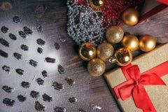 Weihnachtsdekorationen, goldene Bälle, Abdrücke im Schnee Lizenzfreie Stockbilder