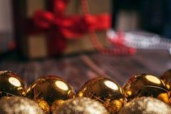 Weihnachtsdekorationen, goldene Bälle, Geschenkbox Stockfotografie