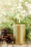Weihnachtsdekorationen mit brennender Kerze, Kiefernkegeln und Tannenzweigen auf hölzernem Hintergrund mit magischem bokeh Effekt Lizenzfreies Stockfoto
