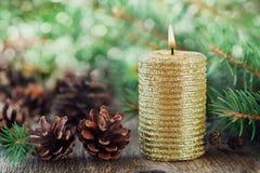 Weihnachtsdekorationen mit brennender Kerze, Kiefernkegeln und Tannenzweigen auf hölzernem Hintergrund mit magischem bokeh Effekt Stockbild