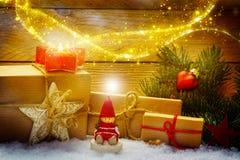 Weihnachtsdekorationen mit Geschenken im Schnee vor Holz Lizenzfreie Stockbilder