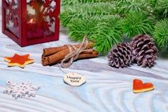Weihnachtsdekorationen mit Schale heißem Kakao, Lampe mit Kerze, Zimtstangen, Kiefer, Tannenzweig auf hölzerner hellblauer Tabell Stockbild